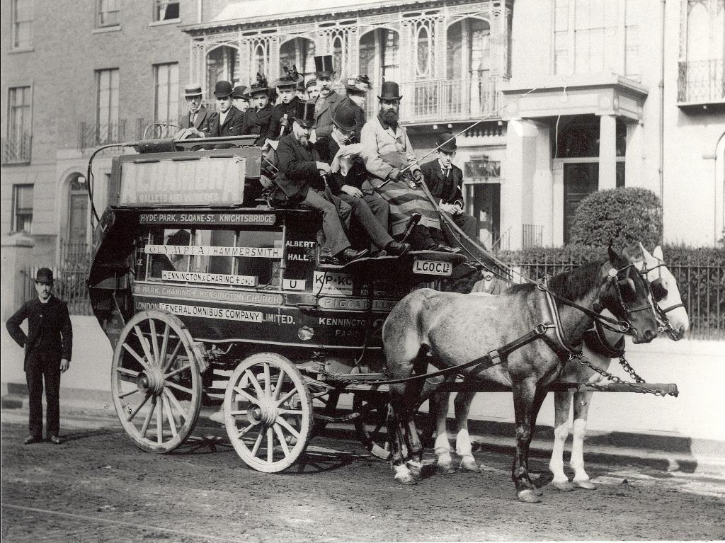 Men in top hats sitting on a horse drawn omnibus
