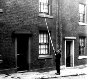 A knocker up with his pole tapping a window.