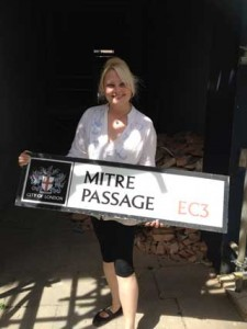 Tour guide Lindsay Siviter holding the Mitre Passage sign.