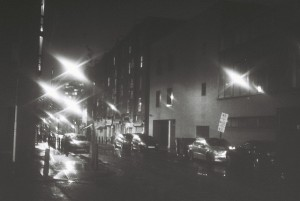 A black and white photo showing Goulston Street at night.