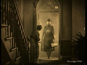 A still from the film The Lodger showing a lady opening the door to Jack the Ripper.