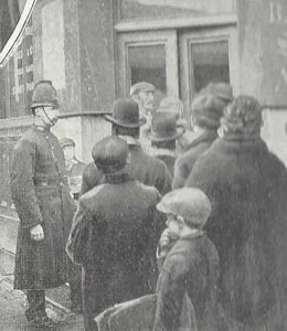 A Police Constable keeps and eye on a group of men.