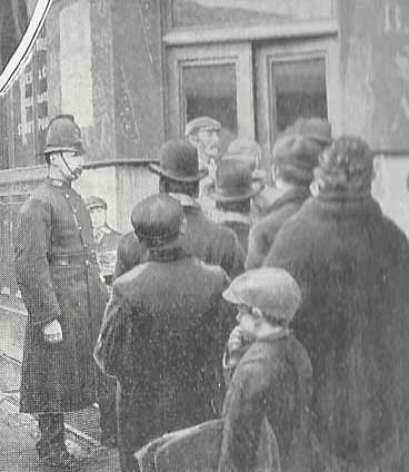 A PPolice Constable keeps and eye on a group of men.