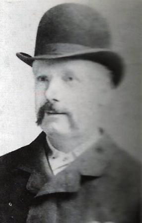 An image of George Lusk wearing a bowler hat.