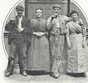 A group of people drinking outside a pub.