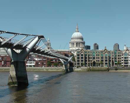 A view of the dome of St Paul's Cathedral with the Millennium Bridge in the foreground.