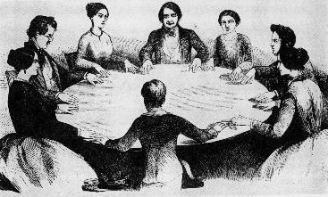 People Gathered round a table holding a seance.