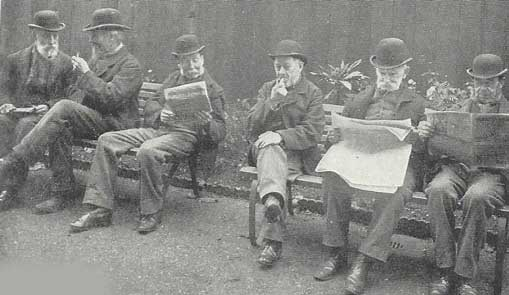 Men reading newspapers and smoking pipes in a Workhouse yard.