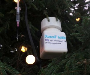 A view of two decorations showing a pill bottle and a syringe.