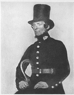 An early police onstable in a top hat and his blue uniform.