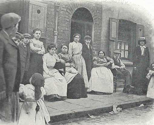 A group of East End residents gather outside their houses in the late 19th century.