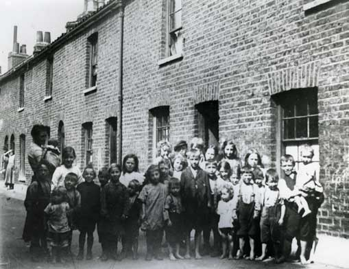 A group of Victorian East Enders gather outside their houses.