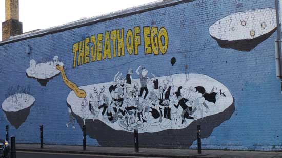 "A giant wall paiting showing figures dancing on an asteroid above which in yellow letters it reads ""The Death of Ego""."