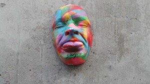 A multi-coloured face that can be seen on a wall in Hanbury Street.