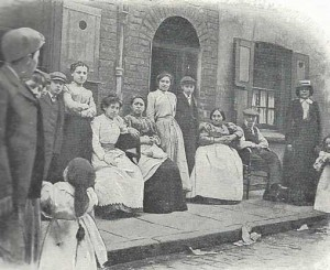 A group of East End men and women pose outside their houses.