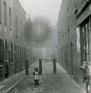 A little girl in a white dress stands in front of a line of three bollards in an East End slum.