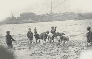 A group of child mudlarkers scavenge on the banks of the River Thames at low tide.