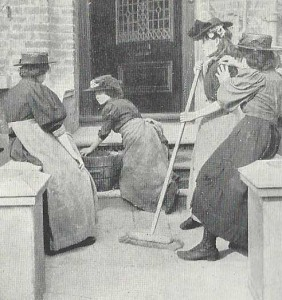 Women clean the steps of a house