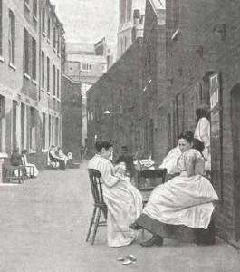 Women wearing white aprons sit in Green Dragon Yard in Whitechapel.