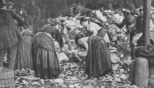 A group of people rummage amongst the detritus of a dust mound.