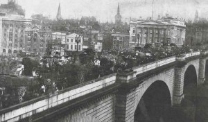 A view of the Victorian Lonodn Bridge with horses and carts crossing it.