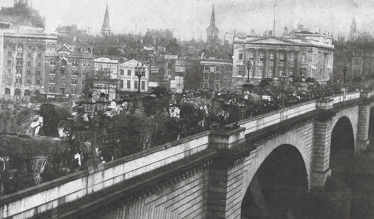 A view of the Victorian London Bridge with horses and carts crossing it.