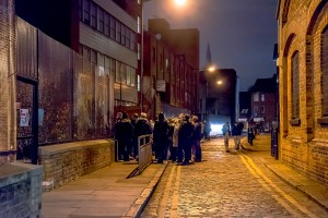 The group gathers around their guide to hear the story of the Jack the Ripper murders.