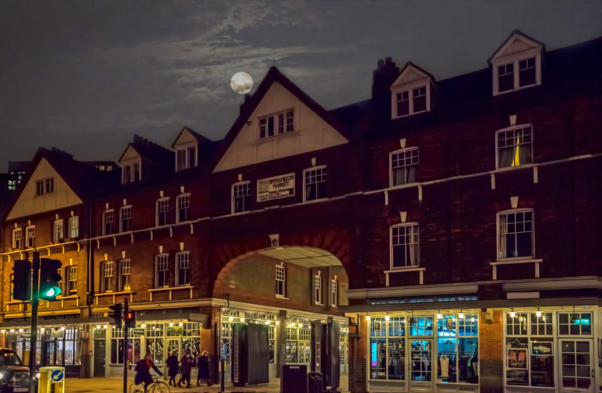 A view of Spitalfields Market by night with the moon above it.