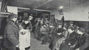 A group of people sitting and being served tea in a common lodging house.