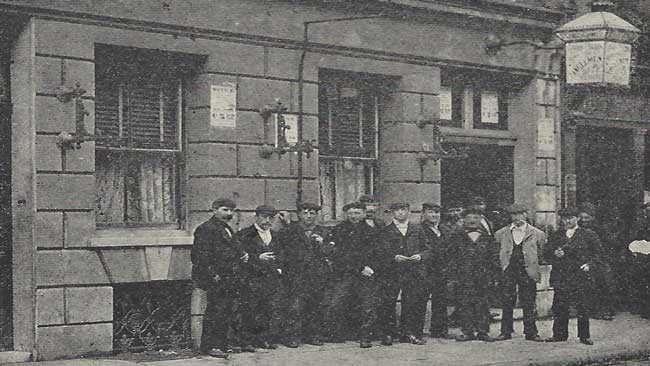 A group of men standing in front of a Common Lodging House.