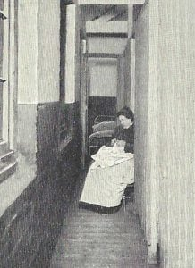 A woma sits by the couples cubicles of a Spitalfields Common Lodging House.