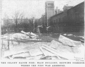 A photo showing the damaged buildings with the main Colney Hatch Asylum building in the background.