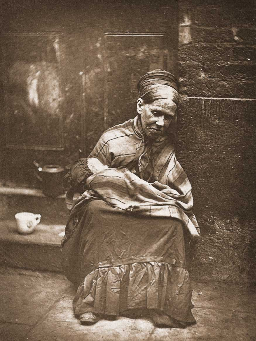 A lady sits on a step, a shawl wrapped around her shoulders, a bundle on her lap.