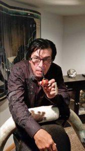 Randy Williams smoking a Sherlock Holmes type pipe.