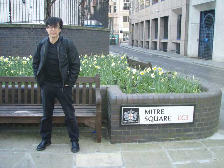 Randy standing by the sign in Mitre Square.