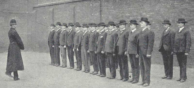 A line of recruits standing to attention in front of a sergeant.