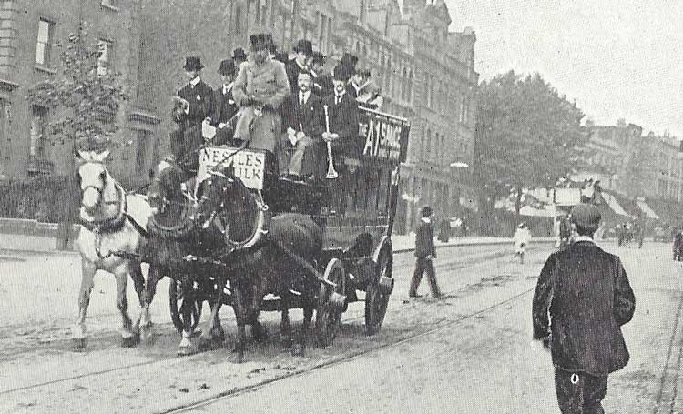 A horse pulls an omnibus through a London street.
