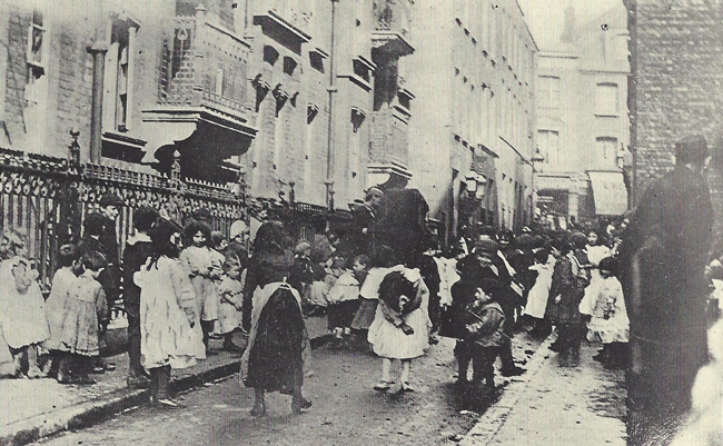 People around an organ player in the streets of Whitechapel.