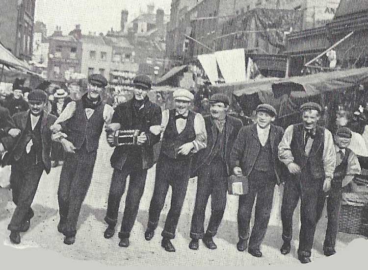 A line of men singing and dancing.