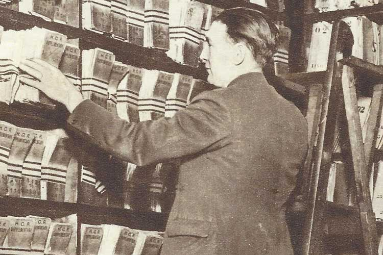 A man on a ladder looking at files of fingerprints.