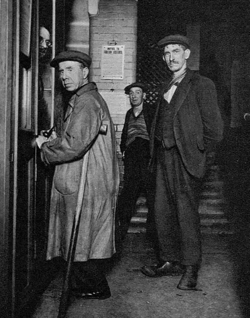 Men in coats and flat caps paying thier admission fee for the lodging house.