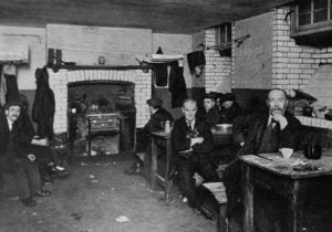 Men sitting at the tables in a lodging house kitchen.