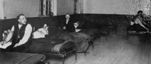 A group of men sitting on their beds in a comon lodging house.