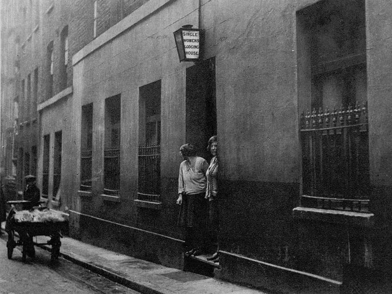 Two women looking out of the doorway of a common lodging house.