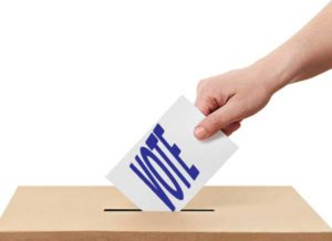 A hand placing a vote into a box.
