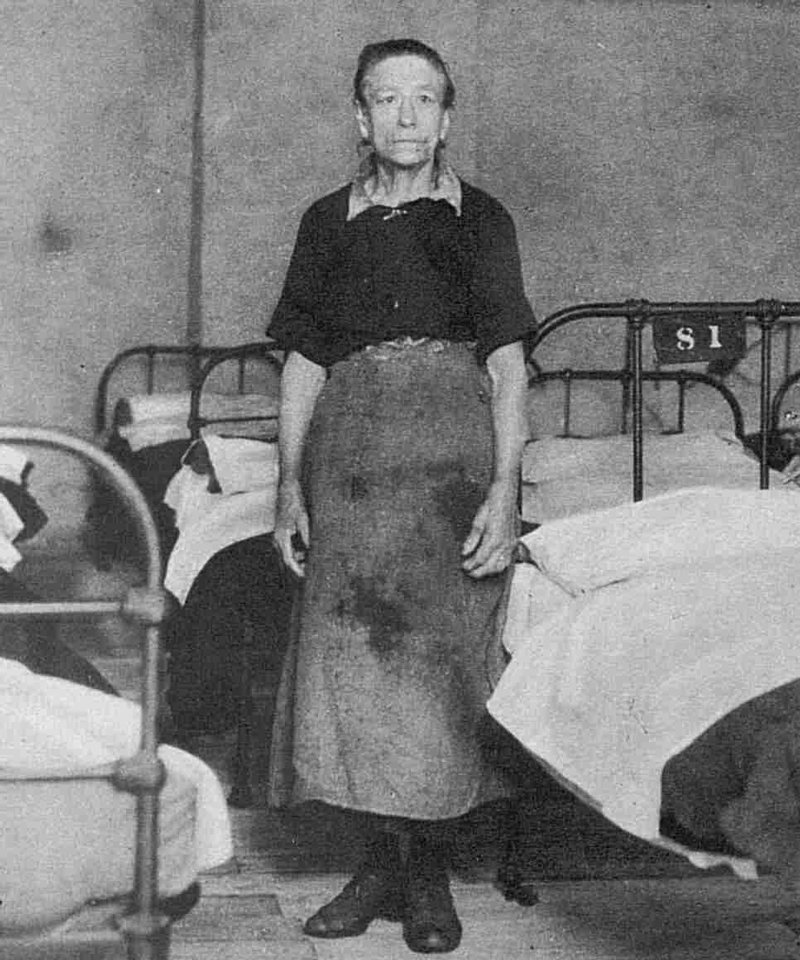 A female attendant stands by a bed at a common lodging house.