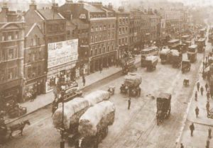 A busy High Street with wagons loaded with hay.