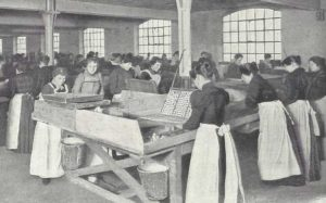 Girls in white aprons working in a factory.