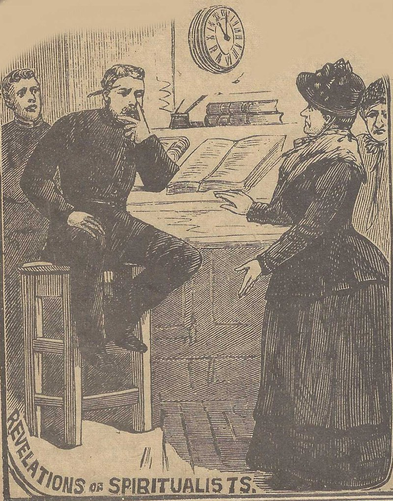 A lady spiritualist dressed in black talks to a seated policeman.
