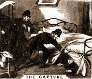 Two police officers find the prisoner under the bed.